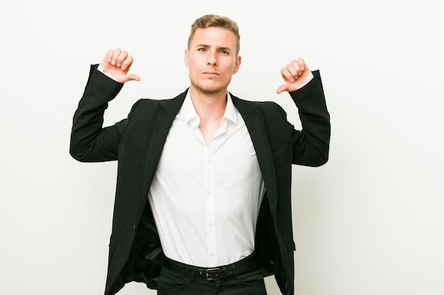 El hombre de negocios caucásico joven se siente orgulloso y seguro de sí mismo, ejemplo a seguir. Foto Premium