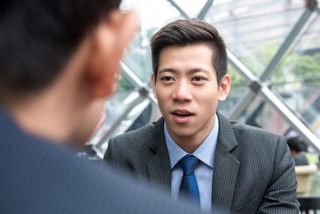 Hombre de negocios chino asiático hermoso joven que habla con su socio Foto Premium