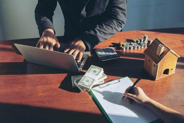 Hombre de negocios comprando y vendiendo casas y concepto de precios inmobiliarios. empresa que firma un contrato de venta de casa Foto Premium