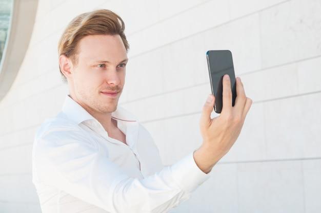 Hombre de negocios confidente que presenta y que toma la foto del selfie al aire libre Foto gratis