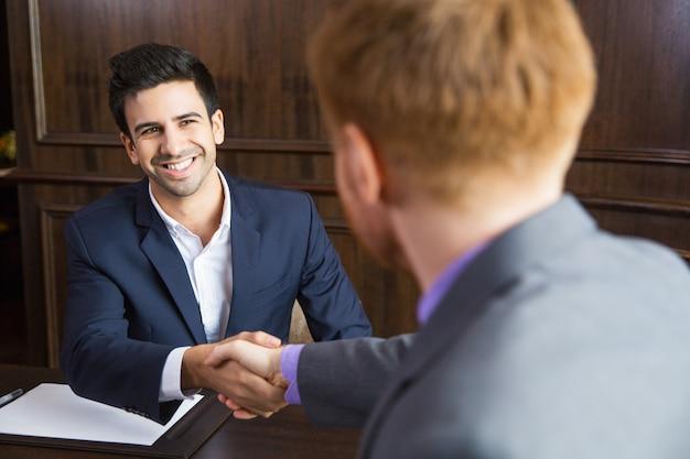 Hombre de negocios dándole la mano a otro hombre de negocios Foto gratis