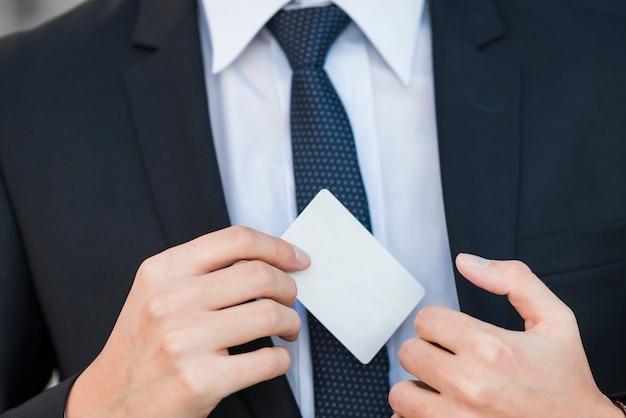 Hombre de negocios elegante enseñando tarjeta de visita Foto gratis