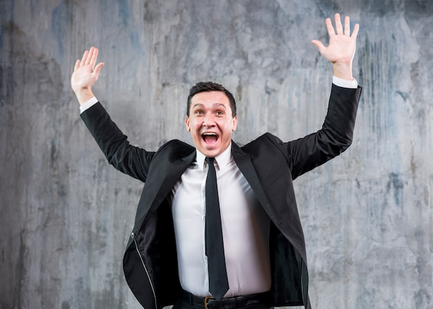 Hombre de negocios elegante joven que levanta las manos y la sonrisa Foto gratis