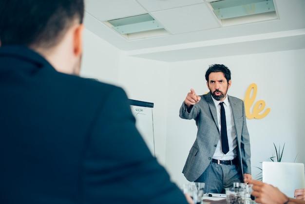 Hombre de negocios enfadado señalando a su empleado Foto gratis