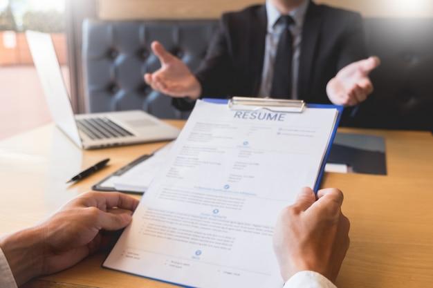 Hombre de negocios escuchar a un joven atractivo explicando sobre su perfil candidato entrevista respuestas Foto Premium