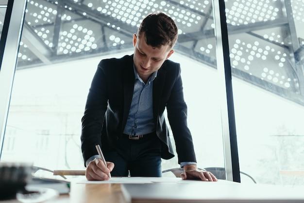 Hombre de negocios exitoso firmando documentos en una oficina moderna Foto gratis