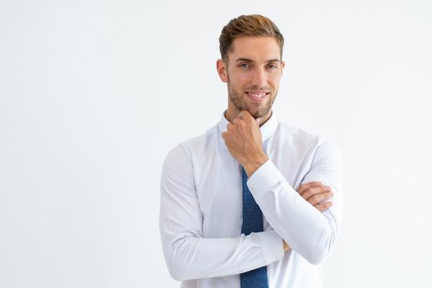 Hombre de negocios feliz tocando barbilla y mirando a cámara Foto gratis