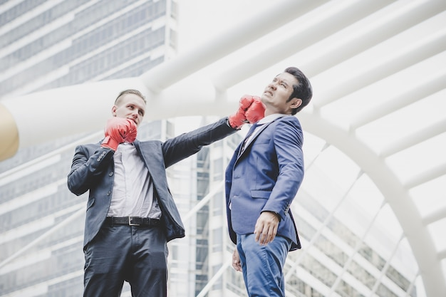 Hombre de negocios con los guantes de boxeo rojos listos para luchar a su compañero de trabajo. Foto gratis