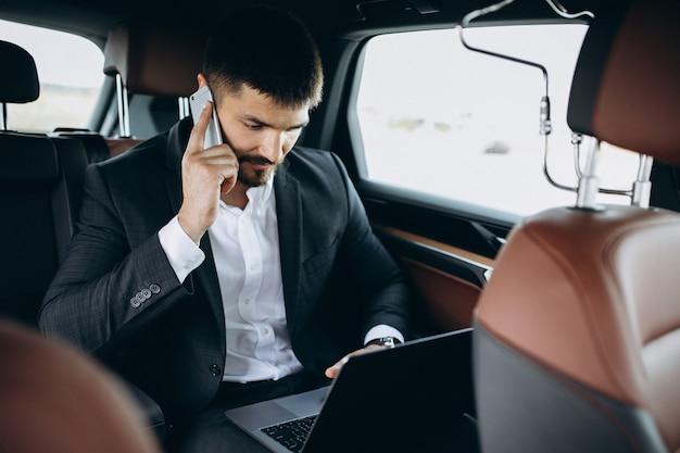 Hombre de negocios guapo trabajando en una computadora en el coche Foto gratis
