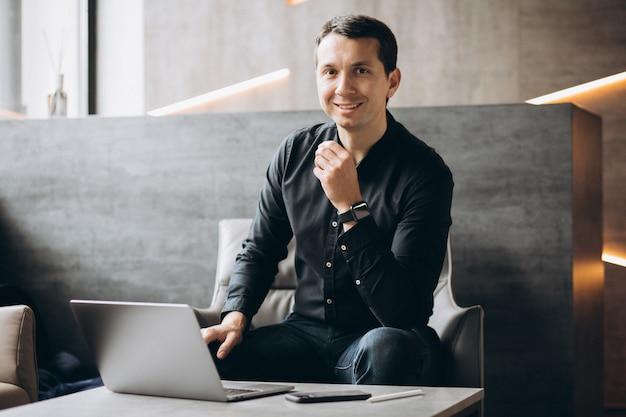 Hombre de negocios guapo trabajando en la computadora en la oficina Foto gratis