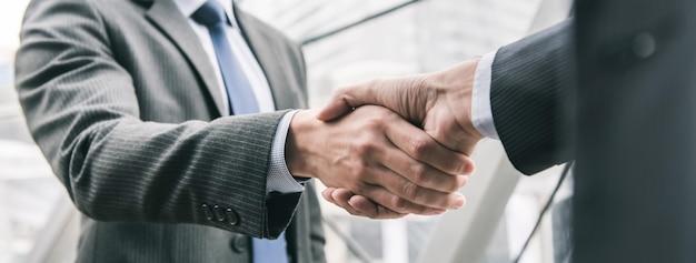 Hombre de negocios haciendo apretón de manos con pareja Foto Premium