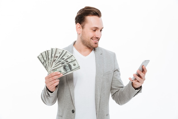 Hombre de negocios hermoso joven alegre que sostiene el dinero y que usa el teléfono móvil. Foto gratis
