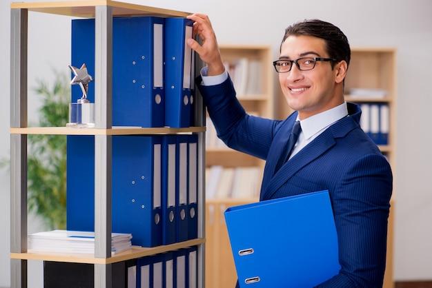 Hombre de negocios hermoso que se coloca al lado de estante Foto Premium