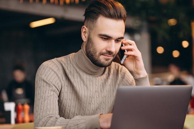 Hombre de negocios hermoso que trabaja en la computadora y que bebe el café en un café Foto gratis