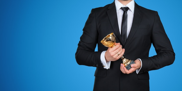 Hombre de negocios irreconocible con un trofeo de oro. concepto de éxito Foto Premium