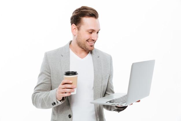 Hombre de negocios joven alegre que bebe el café usando la computadora portátil Foto gratis
