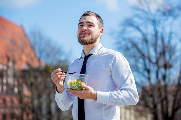 Hombre de negocios joven en camisa y lazo con la caja de almuerzo de la ensalada Foto Premium