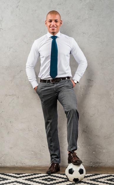 Hombre de negocios joven confiado con sus manos en el bolsillo y pie en balón de fútbol contra la pared de cemento gris Foto gratis