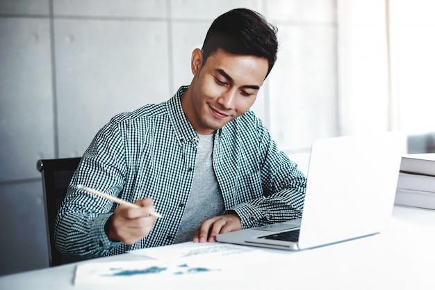 Hombre de negocios joven feliz que trabaja en la computadora portátil del ordenador en oficina. sonriendo y escribiendo en papel Foto Premium