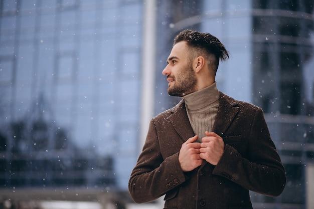 Hombre de negocios joven hermoso afuera en invierno Foto gratis