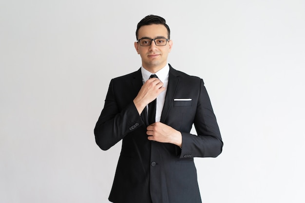 Hombre de negocios joven hermoso elegante confiado que ajusta la corbata y que mira la cámara. Foto gratis