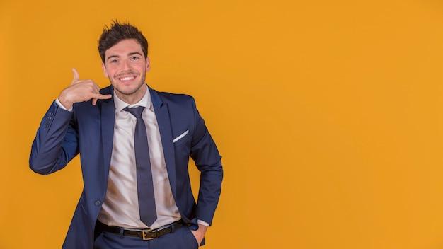 Hombre de negocios joven con la mano en su bolsillo que hace gesto de la llamada contra un contexto anaranjado Foto gratis