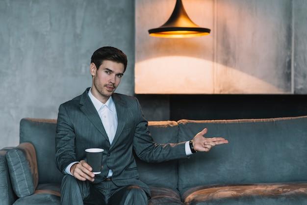 Hombre de negocios joven que se sienta en el sofá que hace gesto del arma de la mano debajo de la lámpara iluminada Foto gratis