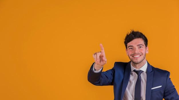 Hombre de negocios joven sonriente contra señalar su dedo hacia arriba contra fondo anaranjado Foto gratis
