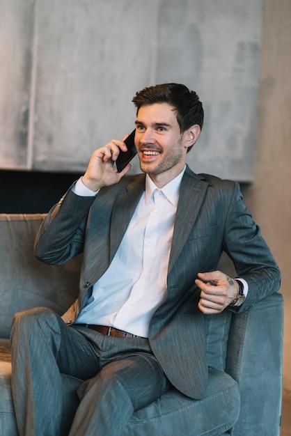 Hombre de negocios joven sonriente que se sienta en el sofá que habla a través del teléfono móvil Foto gratis