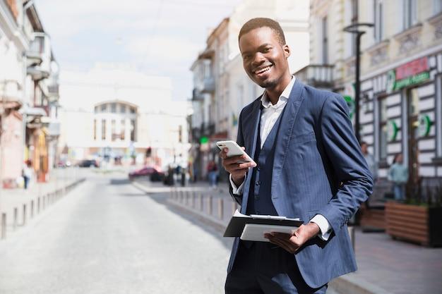Hombre de negocios joven sonriente que sostiene el tablero y el teléfono móvil en la mano que se coloca en el camino en ciudad Foto gratis