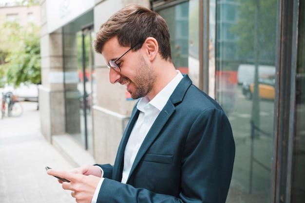Hombre de negocios joven sonriente que usa smartphone Foto gratis