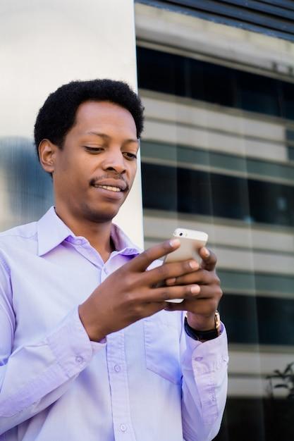 Hombre de negocios latino usando el teléfono móvil en la ciudad. Foto Premium