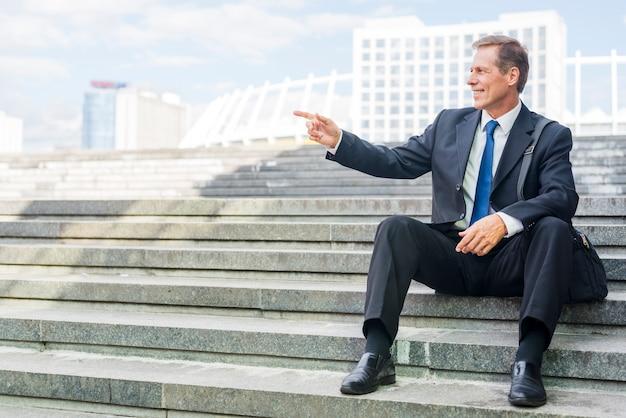 Hombre de negocios maduro sonriente que señala en algo mientras que se sienta en escalera Foto gratis