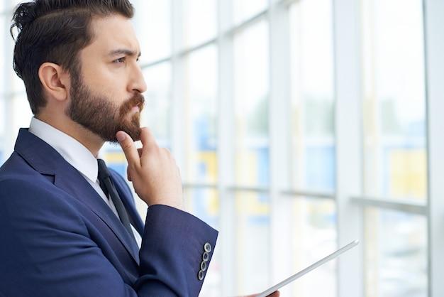 Hombre de negocios mirando a través de la ventana Foto gratis