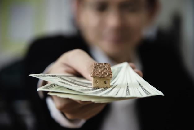 El hombre de negocios muestra dinero el billete de banco hace que el plan financiero invite a la gente a vender o comprar una casa y un automóvil - concepto de seguro de crédito de préstamo de propiedades monetarias Foto gratis