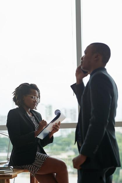 Hombre de negocios negro hablando por teléfono y colega escribiendo en el bloc de notas Foto gratis
