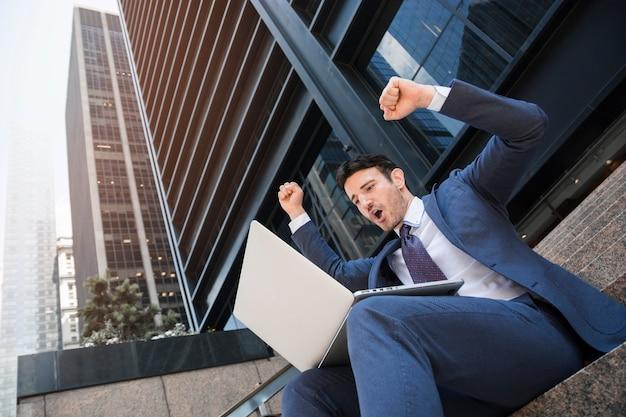 Hombre de negocios con ordenador portátil celebrando el éxito Foto gratis