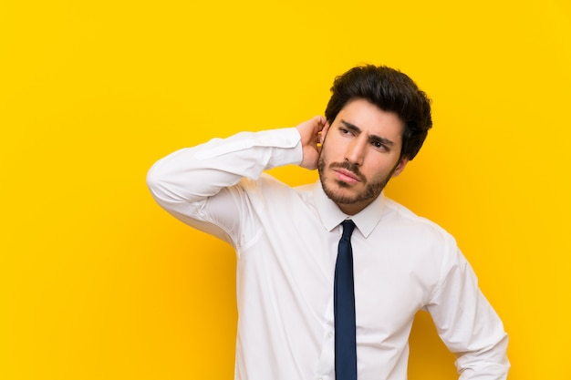 Hombre de negocios en la pared amarilla aislada que tiene dudas y con expresión de la cara confusa Foto Premium