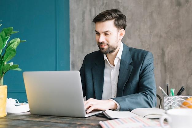 Hombre de negocios positivo que usa la computadora portátil Foto gratis