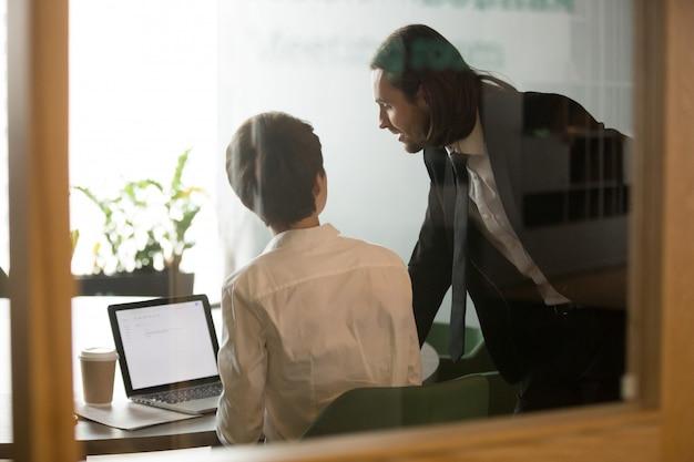 Hombre de negocios que ayuda a la reunión de reflexión de la empresaria que discute el correo electrónico en el ordenador portátil, vista posterior Foto gratis