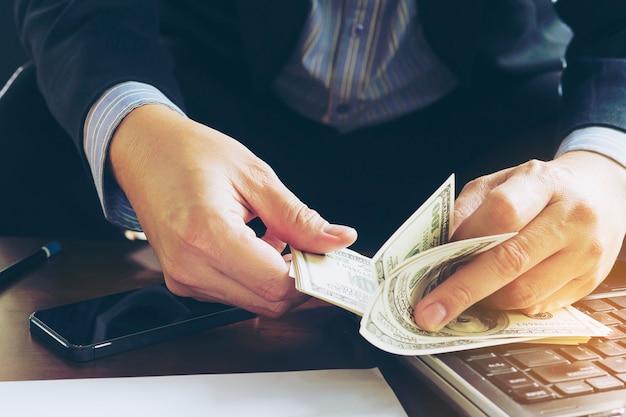 Hombre de negocios que cuenta el billete de banco del dólar - concepto en línea del negocio Foto gratis