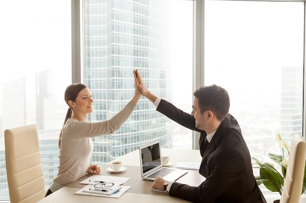Hombre de negocios que da a empresaria el alto cinco en la oficina Foto gratis