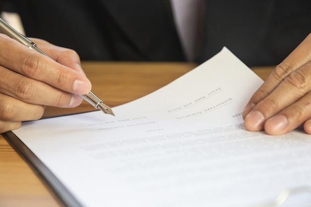 Hombre de negocios que firma un contrato. posee el signo empresarial personalmente. Foto Premium