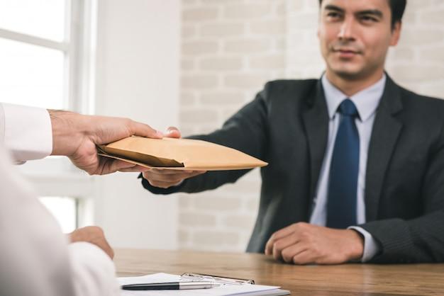 Hombre de negocios que recibe un sobre después de la firma del contrato Foto Premium