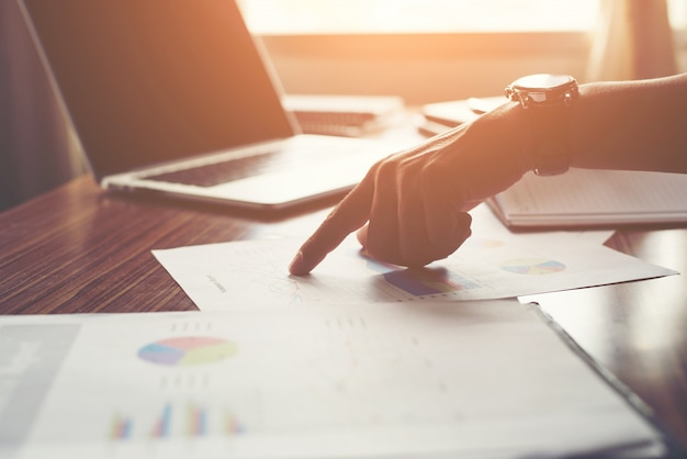 El hombre de negocios que señala el dedo análisis de las estadísticas financieras gráfico Foto gratis