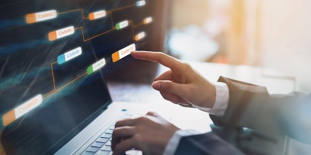 Hombre de negocios que señala la etiqueta de código de icono coherente y la pantalla de desarrollo de aplicaciones en la computadora portátil. Foto Premium