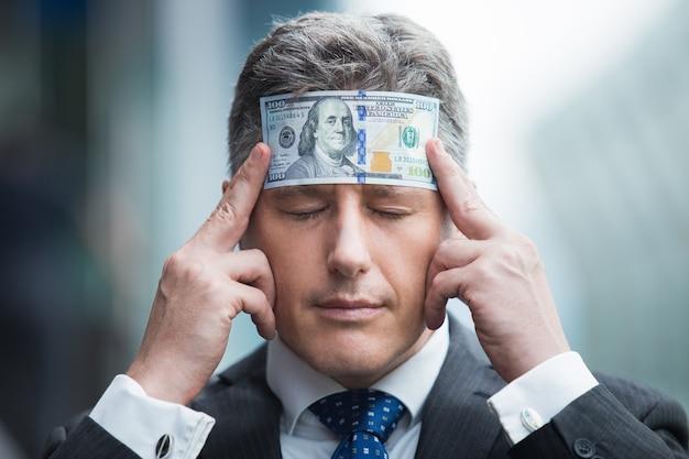 Hombre de negocios que sostiene billetes de banco que muestra negocio Foto gratis