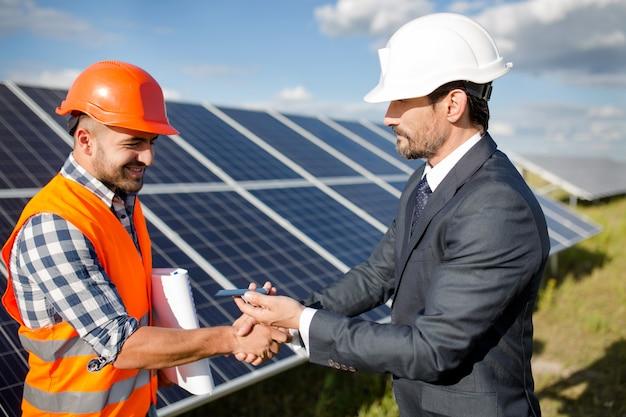 Hombre de negocios que sostiene el detalle fotovoltaico y que sacude la mano a un capataz. Foto Premium