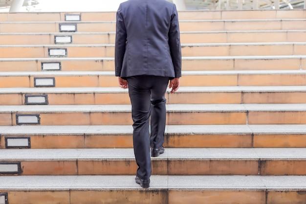 Hombre de negocios que sube las escaleras en una hora punta para trabajar. tiempo de prisa Foto Premium