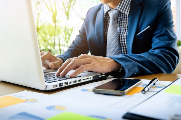 Hombre de negocios que trabaja en la oficina con la computadora portátil, la tableta y los documentos de datos del gráfico en su escritorio Foto gratis